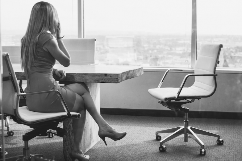 Black and white photo of a slender woman in high heels seated at a conference room table in front of a large bank of windows, with an empty Eames office chair pulled out from the table beside her.