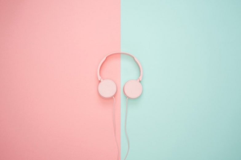 stylized photo of a pair of pink headphones on top of a background that is split in half vertically between light pink and light blue.